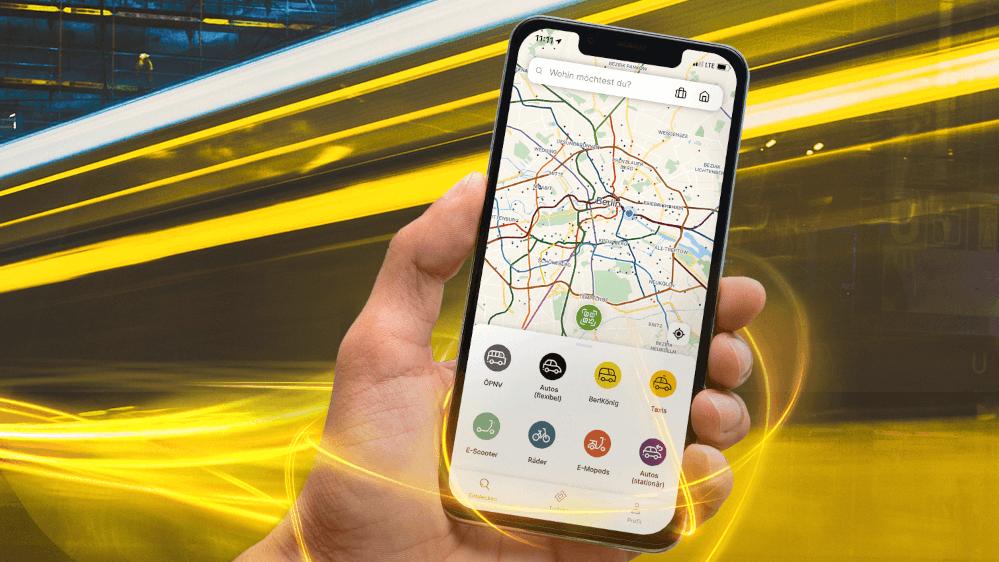 Bild zeigt die Nutzung der Jelbi-App via Handy sowie eine Tram im Hintergrund, die vorbeirauscht